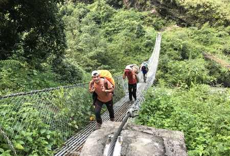 Notre guide à la sortie d'un pont suspendu en direction de Jagat